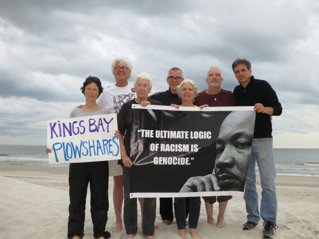 7 older white activists on beach holding protest signs